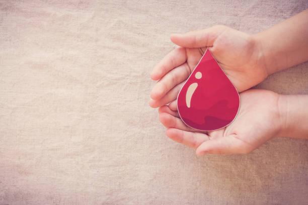 Hände halten Bluttropfen, geben Blutspende, Bluttransfusion, Welt-Blutspendetag, Welt Hämophilie Tag Konzept – Foto