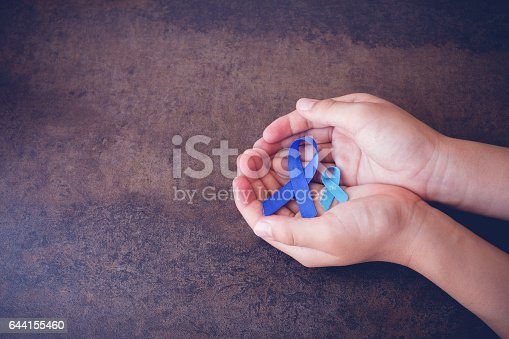 istock hands holding blue ribbons, toning background 644155460
