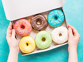 istock hands holding box with donuts 868094188