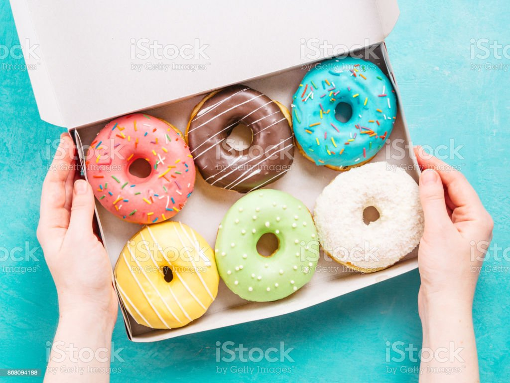 hands holding box with donuts stock photo