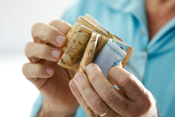 Hands holding Brazilian real notes - Money from Brazil - Notes of Real - Brazil BRL banknote stock photo