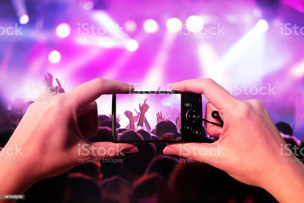 Woman hands taking photos with a pocket camera at a music concert and...