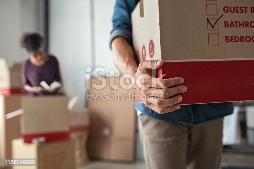 Closeup of man hand holding cardboard at new home. Young man unpacking boxes in new apartment. Man hand carrying carton box while relocating with his girlfriend.