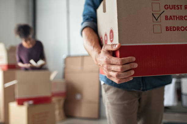 Hands holding cardboard box during relocation stock photo