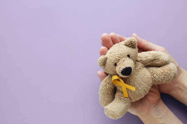 Hände halten Kinder weiches Spielzeug Braunbär mit Gelbgold Band auf lila Hintergrund, Kindheit Krebs Bewusstsein – Foto