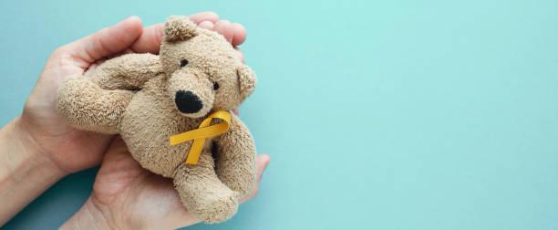 mãos que prendem crianças urso marrom do brinquedo macio com fita amarela do ouro, consciência do cancro da infância - setembro amarelo - fotografias e filmes do acervo