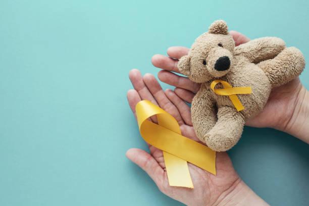 mãos que prendem crianças urso marrom do brinquedo macio com fita amarela do ouro, consciência do cancro da infância - infância - fotografias e filmes do acervo