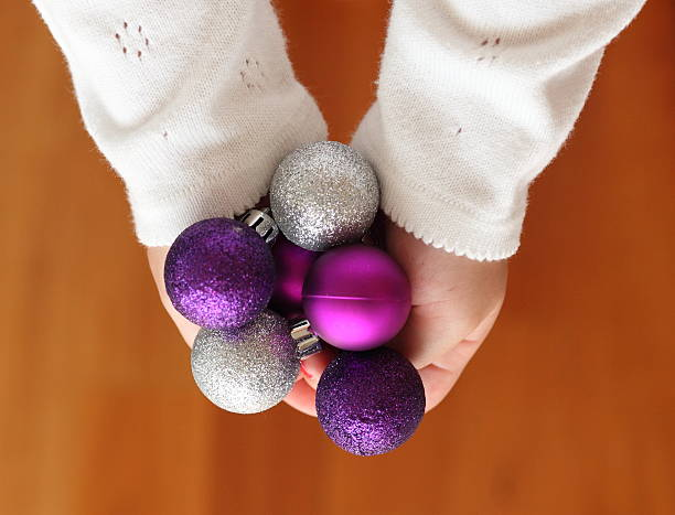 Hands holding Christmas baubles stock photo