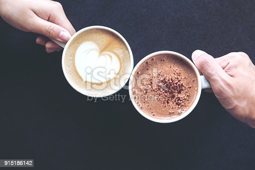istock hands holding coffee and hot chocolate cups with wooden table background 915186142