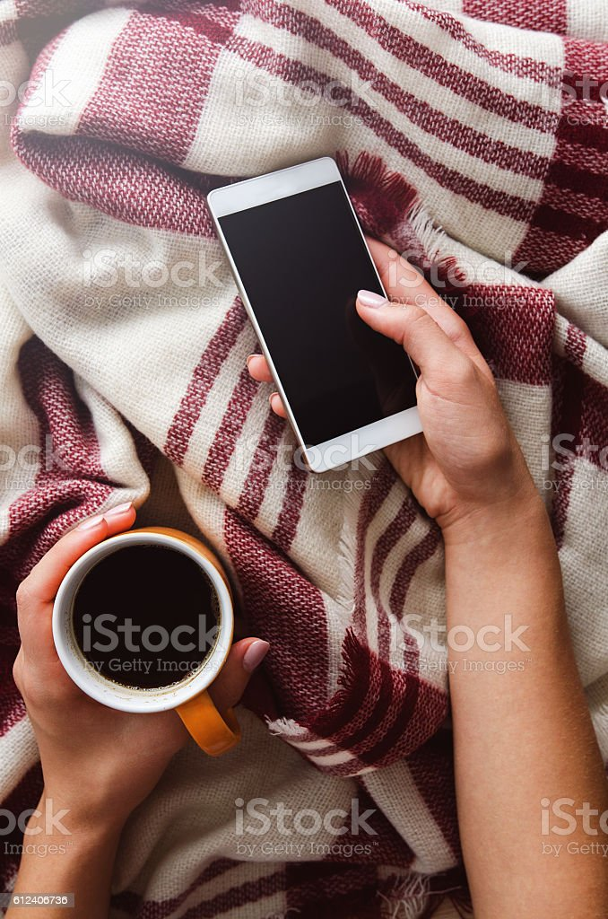 Hands holding coffee and phone in warm bed on autumn stock photo