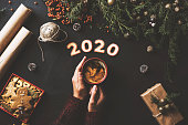 Happy New Year 2020 concept table top flat lay. Woman wearing red sweater holding coffee in red mug. Wrapping paper, jute string, gift box, Christmas ornament, pine cones , firethorn branches and gingerbread cookies on black background.