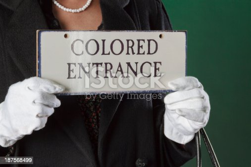 An African American performance artist holding a sign that was significant in the segregation times of the United States in the fifties.