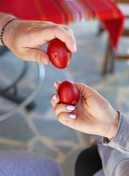 hands holding cracked red Easter eggs - Orthodox greek tradition of cracking eggs - symbolizes Christ resurrection stock photo