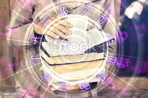 istock Hands holding creative zodiac wheel book 1090110272