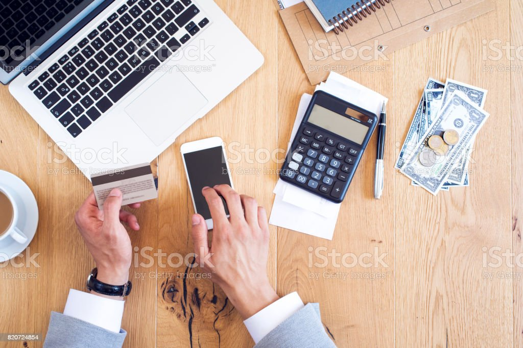 Hands holding credit card and paying bills on table stock photo