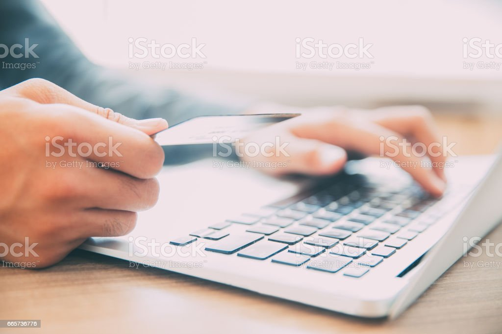 Hands holding credit card and typing on laptop stock photo