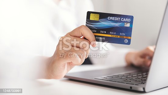 Hands holding credit card and using laptop computer, Businesswoman working at home, Online shopping, E-commerce, Spending money, Internet banking, Work from home concept.