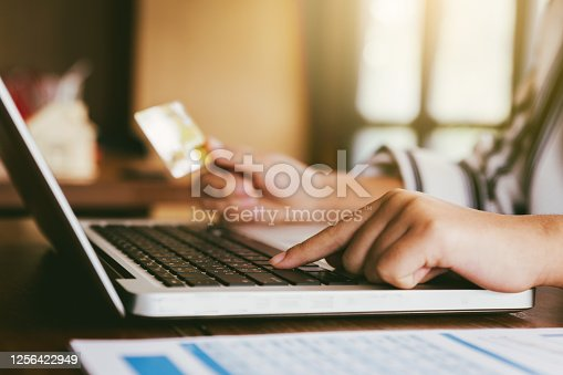 Hands holding credit card and using laptop. Online shopping and small business concept.