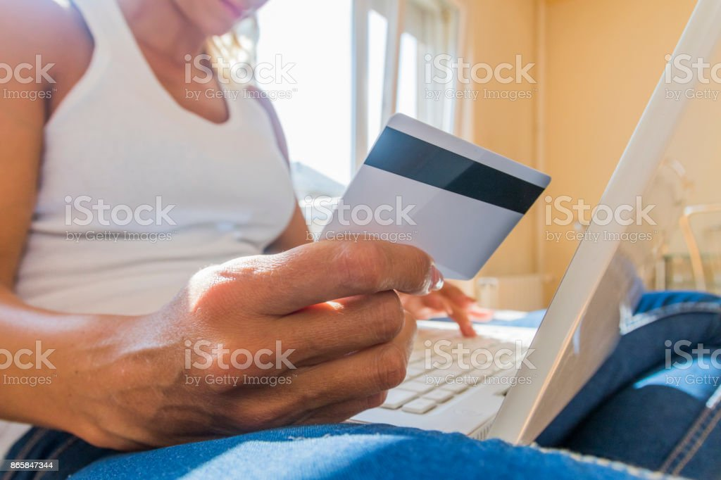 Hands holding credit card and using laptop. Online shopping stock photo
