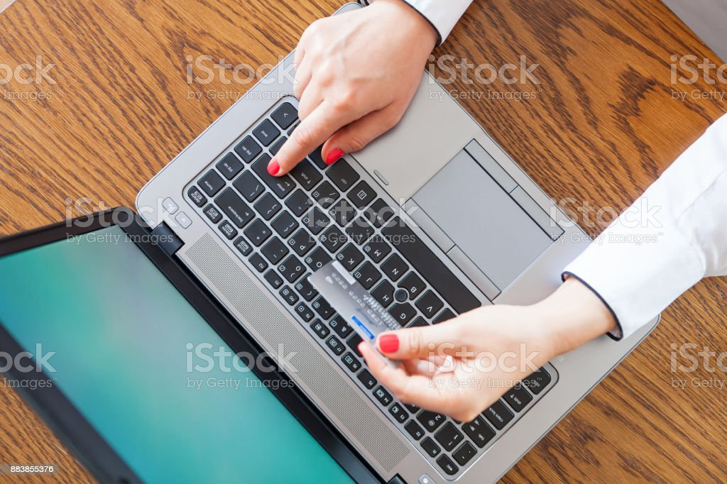 Hands holding credit card and using laptop top view - online shopping stock photo