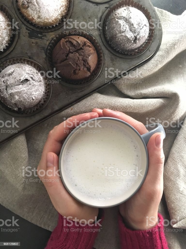 Hands holding cup of milk near baked chocolate muffins stock photo