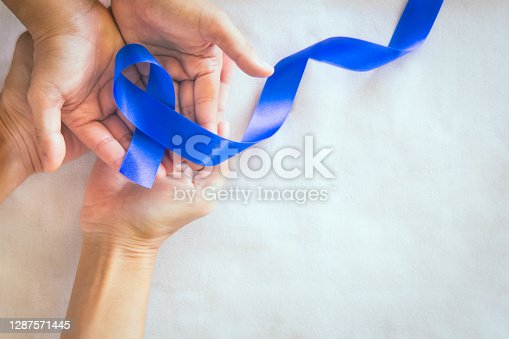 Hands holding deep blue ribbon on white fabric with copy space. Colorectal Cancer Awareness, Colon cancer of older person and world diabetes day, Child abuse prevention. Healthcare, insurance concept.