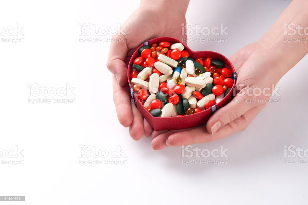 Hands holding different colored medicine and types of pills stock photo