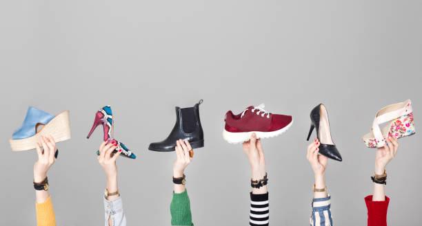 회색 배경에 다른 신발 들고 손 - 신발 뉴스 사진 이미지