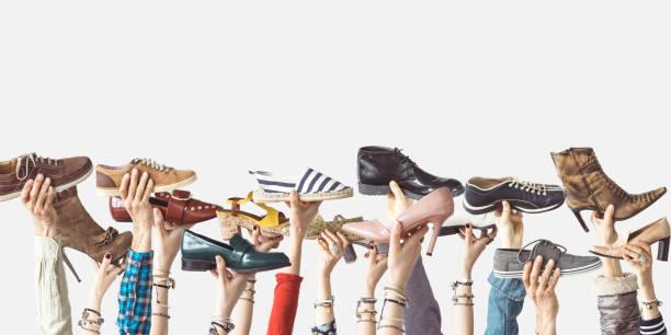 격리 된 배경에 다른 신발 들고 손 - 신발 뉴스 사진 이미지