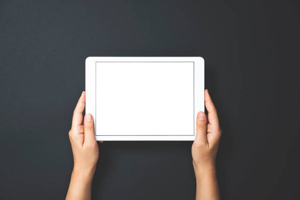 Hands holding digital tablet on black background stock photo