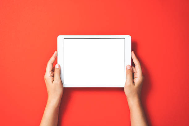 Hands holding digital tablet on red background stock photo