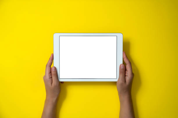 Hands holding digital tablet on yellow background stock photo