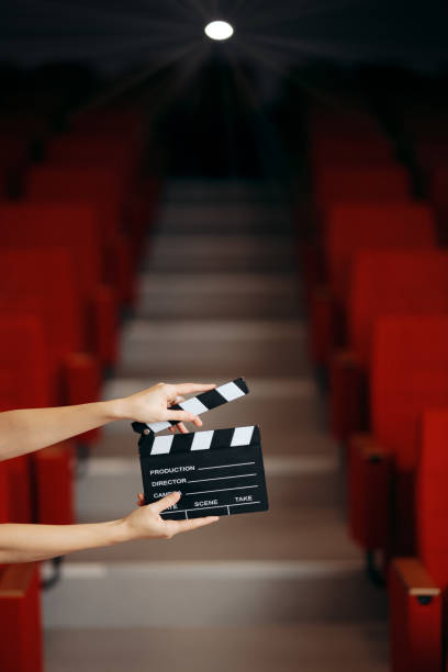 hands holding director movie clapper in cinema theatre - audition stock photos and pictures