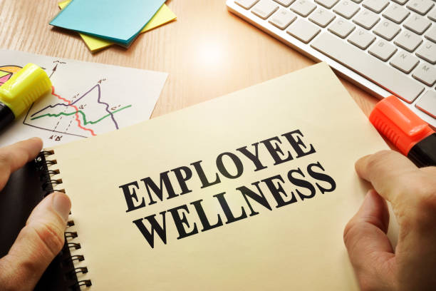 Hands holding documents with title Employee Wellness. stock photo