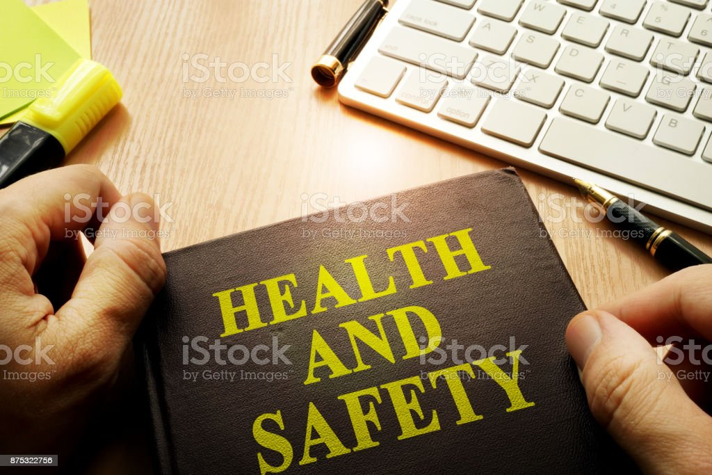 Hands holding documents with title health and safety. stock photo