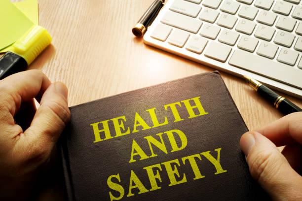 händer som håller dokument med titeln hälsa och säkerhet. - arbetssäkerhet bildbanksfoton och bilder