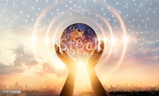 istock Hands holding earth and wave circle global structure network connection and data exchanges customers worldwide on city sunset background. Innovation. Creative and inspiration. Idea and imagination. Networking and technology concept. Elements of this image 1127243280
