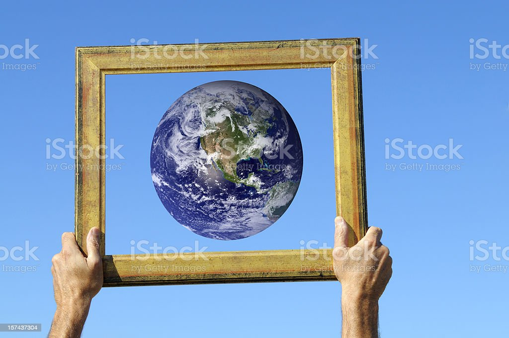 Hands Holding Earth in Frame Blue Sky stock photo