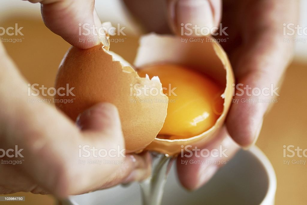Hands holding egg shell with egg yolk separated stock photo
