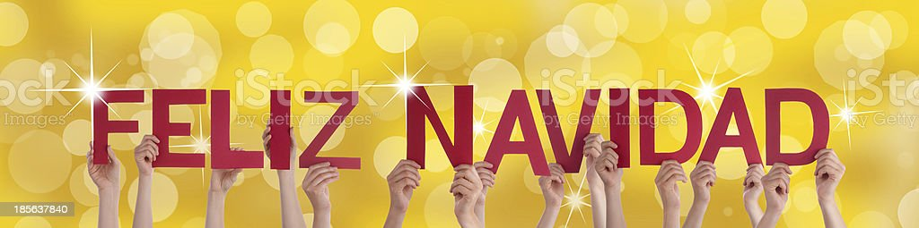 Hands Holding Feliz Navidad with Golden Background royalty-free stock photo