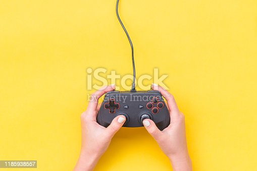 Hands Holding Gamepad. Black joysticks on yellow background. Computer game competition. Gaming concept. Place for text. Flat lay, top view