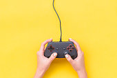 istock Hands Holding Gamepad. Black joysticks on yellow background. Computer game competition. Gaming concept. Place for text. Flat lay, top view, copy space. 1185938557