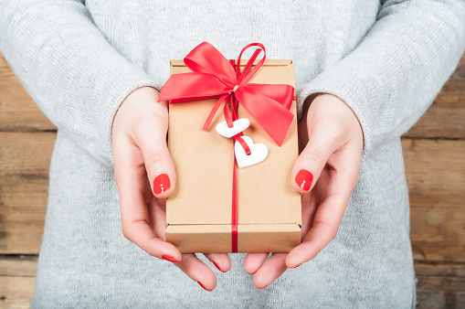Hands holding gift in kraft box on a wooden background. The concept of St. Valentine's day, weddings, engagements, Mother's Day, birthday, New Year, Christmas, holidays.