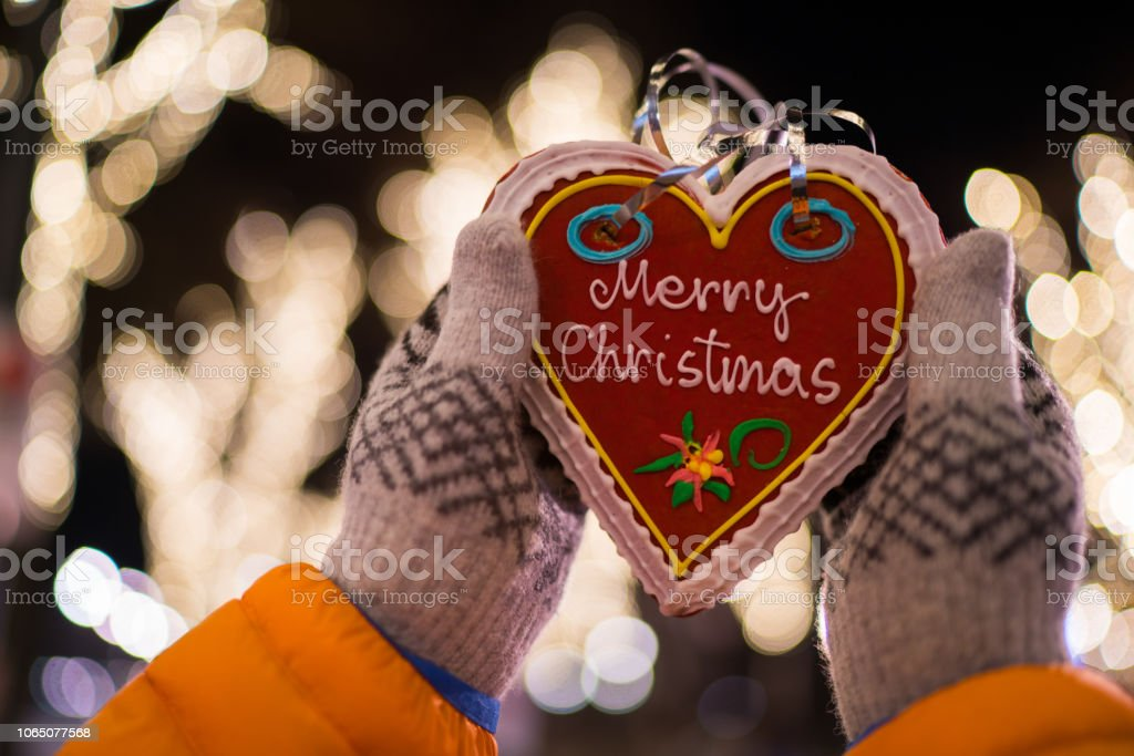 merry christmas heart shaped gingerbread with text hands holding...