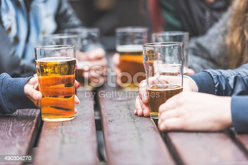 istock Hands holding glasses with beer on a table in London 490304270
