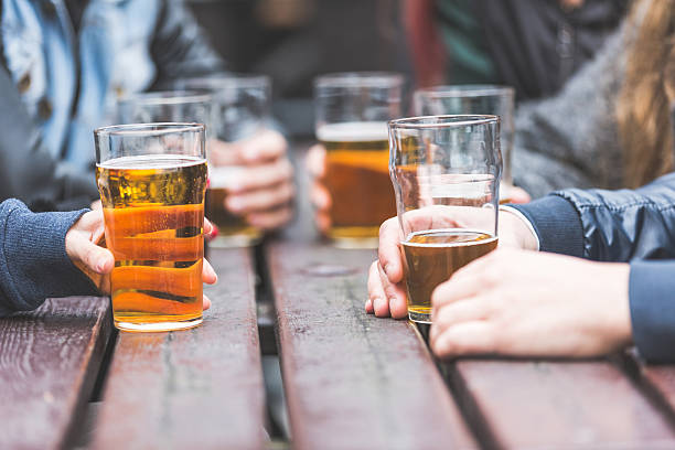 hands holding glasses with beer on a table in london - beer alcohol stock pictures, royalty-free photos & images