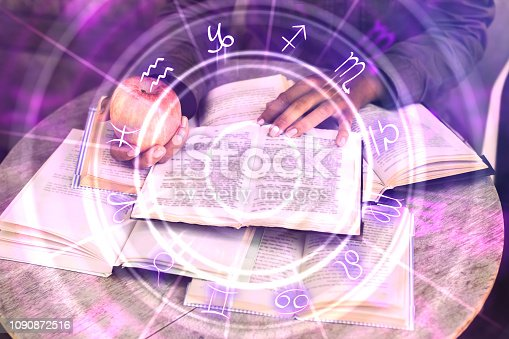 istock Hands holding glowing zodiac wheel book 1090872516