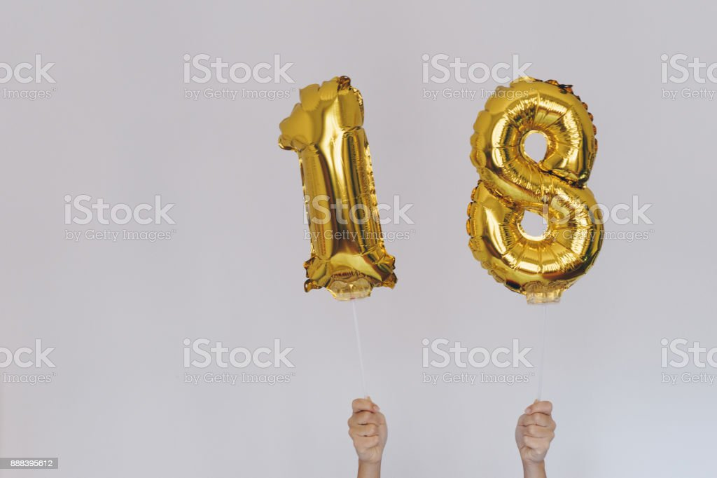 Hands holding golden 18 balloons, new year concept stock photo