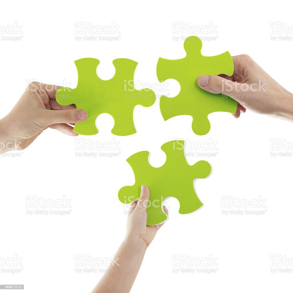 Hands Holding Green Puzzle Pieces stock photo