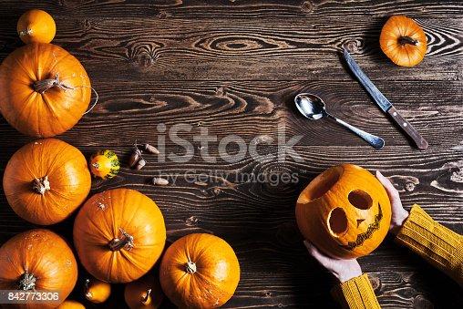 istock Hands holding Halloween pumpkin over wooden background 842773306